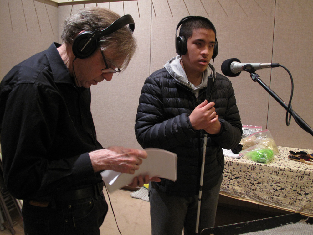Jesse Minkert and a workshop participant record his voice in the studio